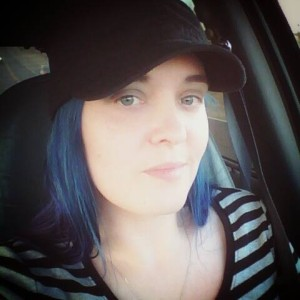 selfie of young woman with blue hair, wearing a shirt with black and white horizontal stripes and a black hat
